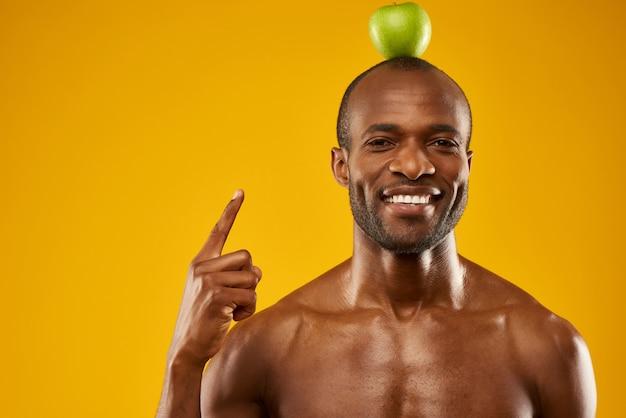 男は頭の上にリンゴを保持します。グリーンワールドのコンセプトです。