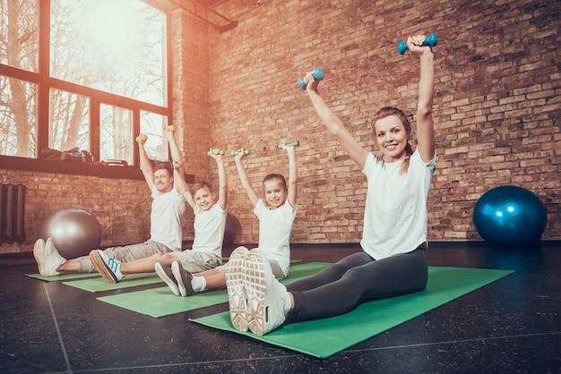 ジムのカーペットの上のスポーツ家族。ダンベル体操。