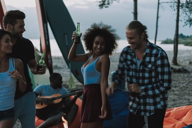 カップルはビーチで踊ります。アフロアメリカンギタリスト。