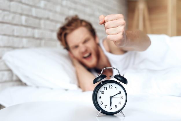 若いイライラ男は目覚まし時計をオフに手を差し伸べる。