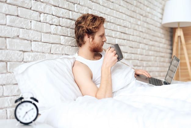 成功した実業家はコーヒーを飲みながらベッドで働いています。