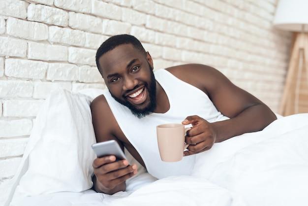 男はベッドブラウジングウェブでコーヒーを飲みます。早朝。