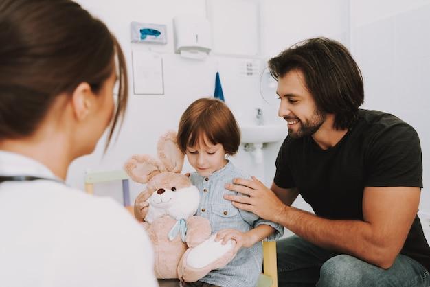 医者のオフィスの子供で男と息子はウサギのおもちゃを保持します。