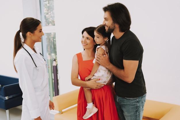 Дружественные педиатр беседует с матерью и отцом
