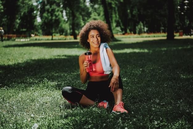 魅力的なアフリカ系アメリカ人の女の子が公園でリラックス。
