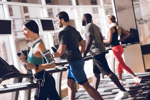 Счастливые люди бегут по беговой дорожке в тренажерном зале.