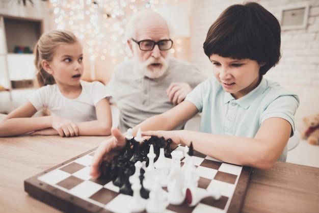 怒っている子の少年が自宅でチェスをしています。