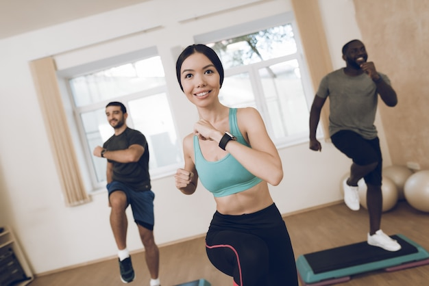 笑顔の運動選手は現代的なジムでフィットネスに取り組んでいます。