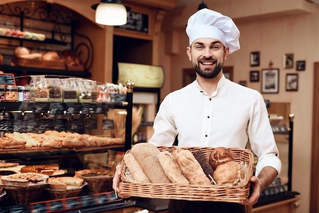 パン屋さんに立っている白い帽子のひげを生やした若い男。