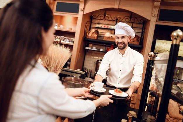 若い男がパン屋で女性にケーキとお茶を売る
