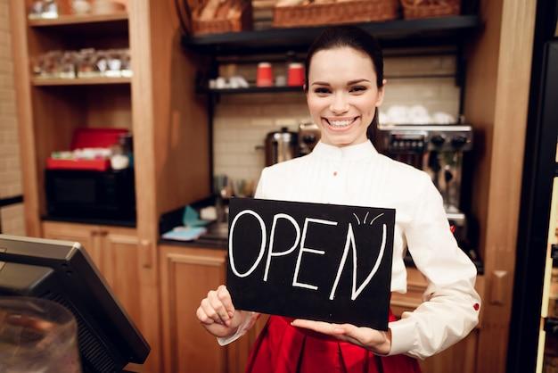 パン屋さんに立っているオープンサインを持つ若い女。