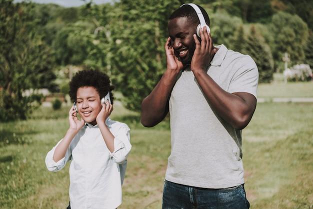 アフロの息子と父親が一緒に音楽を楽しむ。