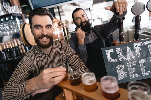 クラフトビールの伝統的なパブ幸せな男性バーテンダー。