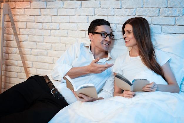 Мужчина и женщина, лежа в постели у себя дома.