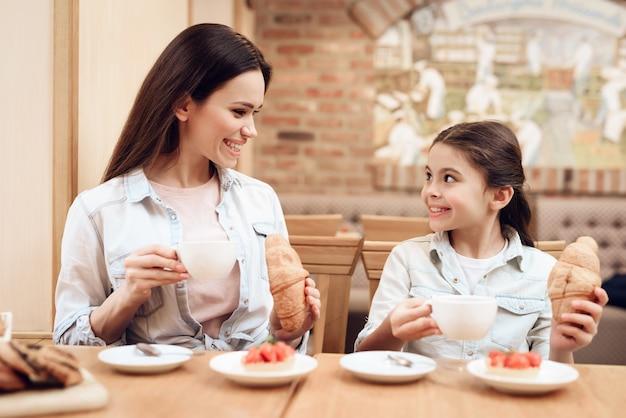 幸せな家族カフェで一緒に食べる。