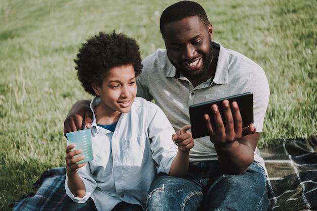 Отец обнимает сына на пикник и мальчика показать на планшете.