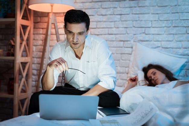 Работа на ноутбуке в постели с молодой женщиной.