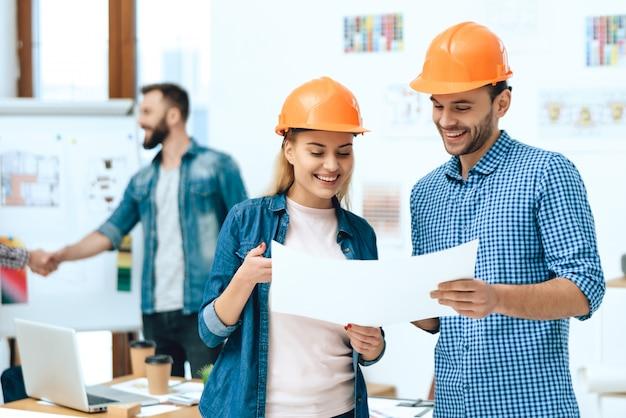 Два дизайнеров архитекторы позируют с бумагами.