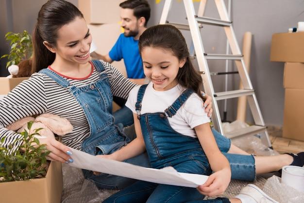 Счастливая мать с маленькой дочерью рассматривает план.