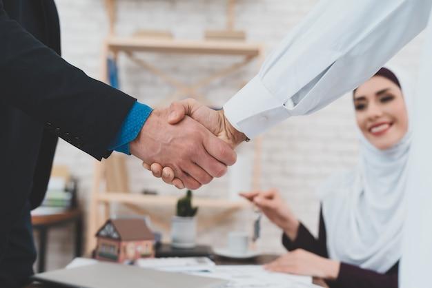 男性ハンドシェイクアラブ人ビジネスパートナーシップ。