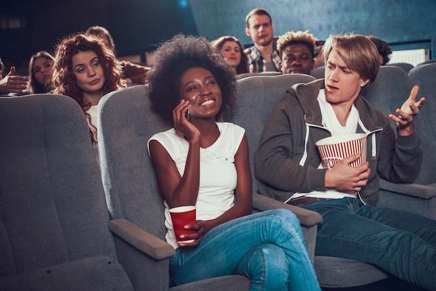 若い女性は映画館で電話で通信します。