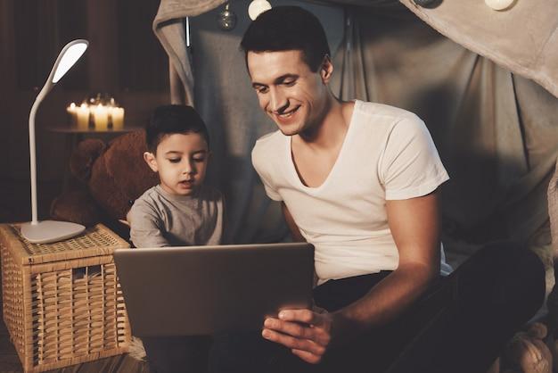 父と息子は自宅で夜にラップトップでビデオを見ています。