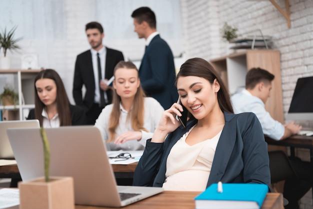 幸せな妊娠中の女性がオフィスで話しています。