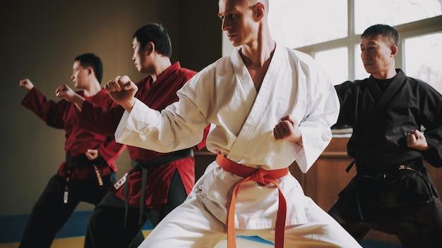 Бойцы в красных и черных поясах делают боевые стойки.