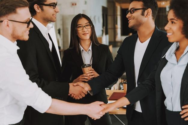 Деловые и деловые женщины пожимают друг другу руки.