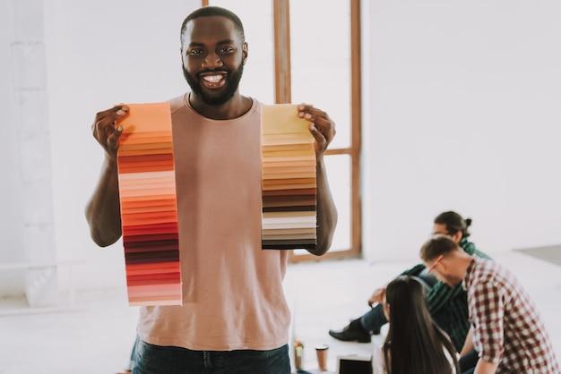 Афро-американский мужчина держит цветовые палитры и улыбается.