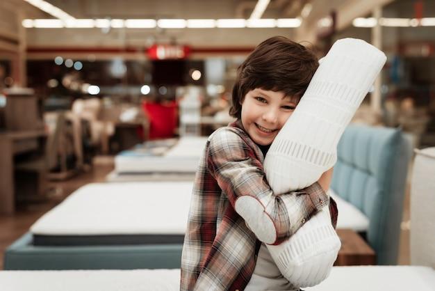 店のベッドの上の小さな男の子抱き枕を笑顔