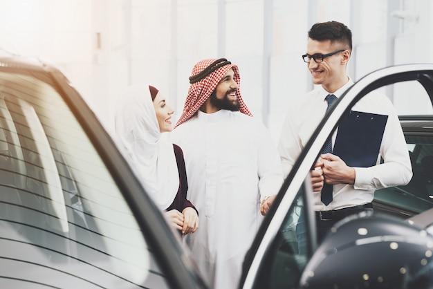 セールスマンはアラブ人と女性に車のクレジットを提供します。