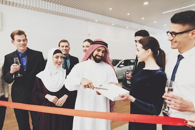アラブのビジネスマンは赤いリボンをカットするはさみを取ります。