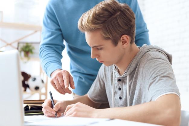 父は息子が宿題をするのを助けます。