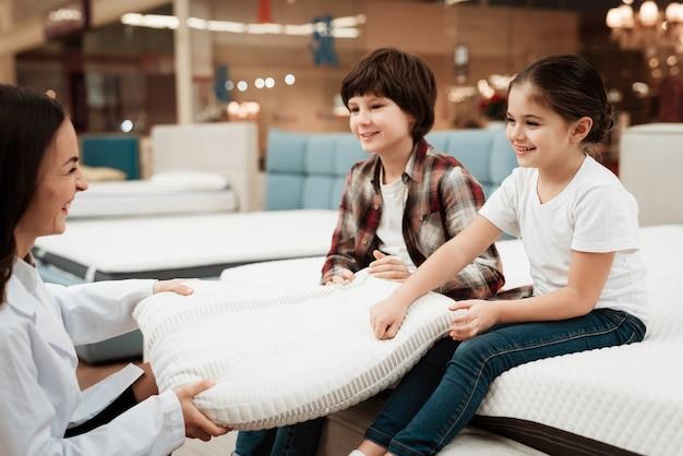 子供に枕を示す女性コンサルタント