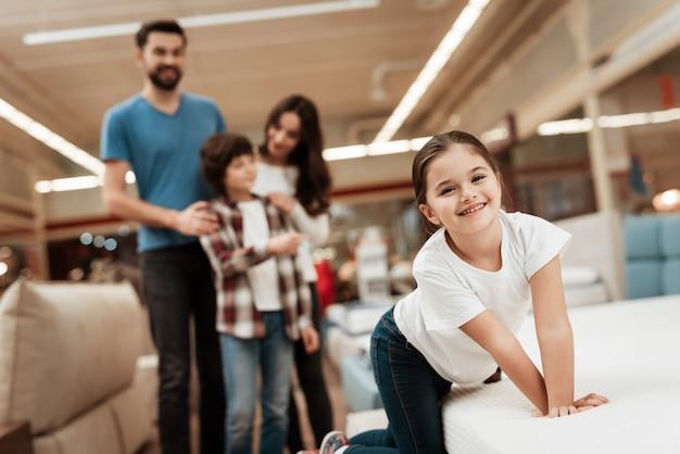 マットレスの店を通して歩く若い笑顔家族
