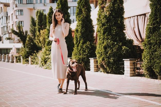 美しい幸せな白人の女の子は彼女の犬と一緒に歩いています。