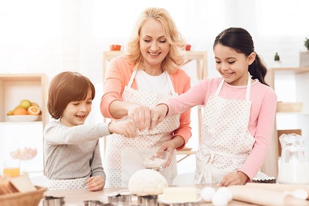 クッキーのための生地をこねる子供とおばあちゃん