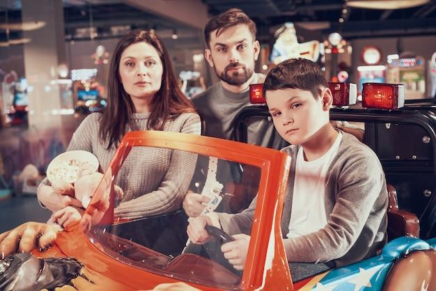 家族、息子がモールでおもちゃの車に座っています。