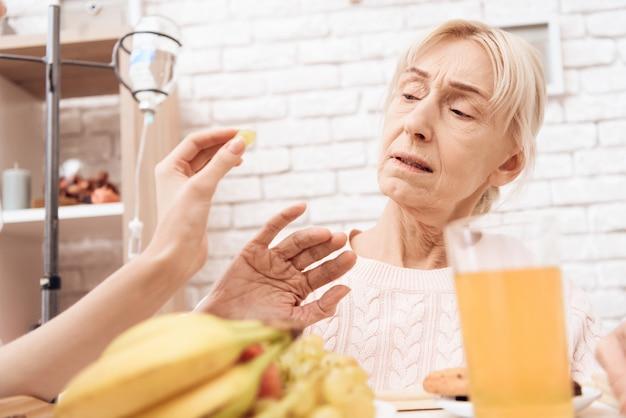 女の子はトレイに朝食をもたらします。女性は食事を拒んでいます。
