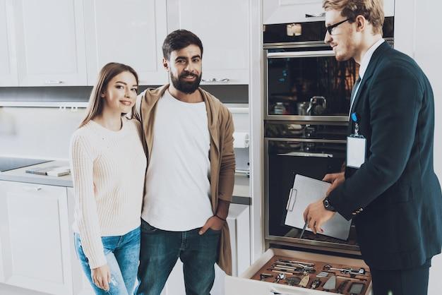 スーツを着た売り手は、作り付けのキッチンを見せています。
