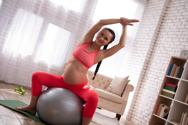 Беременная женщина тренирует живот с мячом.
