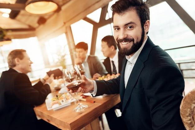 男はワイングラスでポーズします。