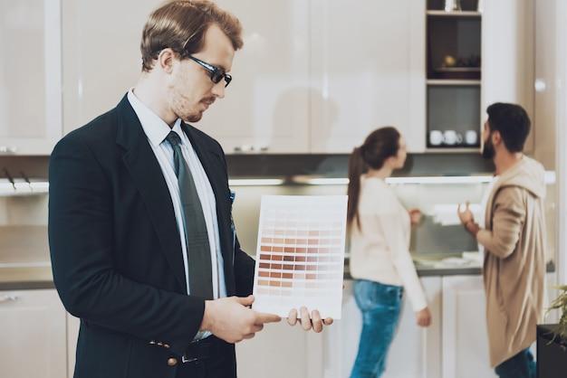 スーツを着た男はキッチン店で色見本を見せています。