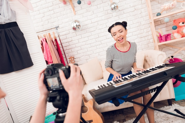 ファッションの女の子がキーボードを弾いて歌う