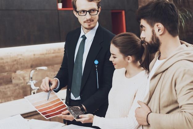 スーツのマネージャーはカップルのクライアントにカラーパレットを見せています。