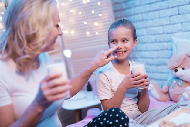 美しい少女はミルクとクッキーを楽しんでいます