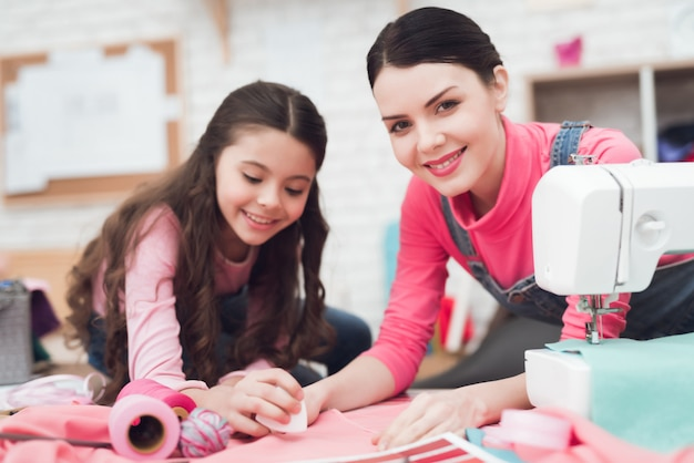 ママと幼い娘が一緒に服を縫います。