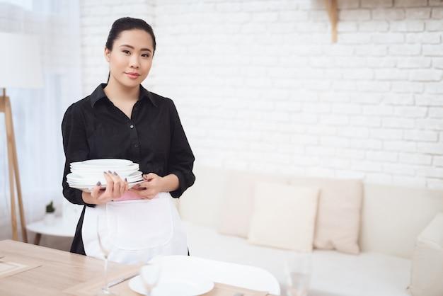 Красивая девушка тайская домработница с белыми тарелками.