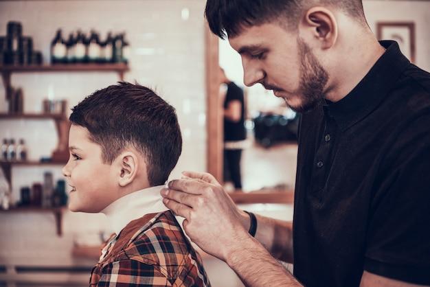Человек парикмахер режет ребенка в парикмахерской.